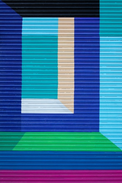 Wall painted in horizontal and vertical stripes or purple. dark blue, green, light blue, turquoise, white and peach.