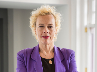 Head and shoulders image of white woman with short curly blonde hair wearing a purple jacket and black top
