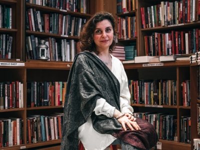 Image description: A woman is sat on a stool facing the camera. She has wavy dark brown, shoulder length hair. She is wearing a white smock top with a grey shawl over her right shoulder. She is sat surrounded by books on wooden book shelves.
