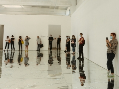 A large white room with a mirrored floor. People stand around the outside, taking photographs and exploring the space.