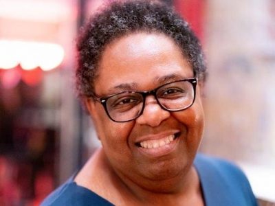 Image description: A woman with short black curly hair, smiling at the camera. She is wearing black rimmed glasses and a dark blue top. The background is blurred