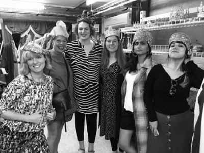 Photo by Tom Freshwater. Left to right, Clore 15 Fellows, Sophie Woolley, Adele Patrick, Kim Simpson, Kate Craddock, Jemma Desai, Sofía Márquez Moreno wear crowns at RSC Costume Hire Shop.
