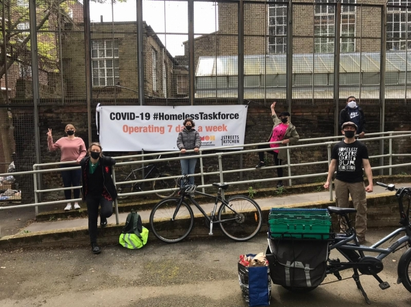 Four women and two men standing several meters apart on a ramp in front of a building. They are wearing face masks and have bicycles with them, standing in front of a large white banner with black and orange writing on it: COVID 19 #HomelessnessTaskforce Operating 7 days a week