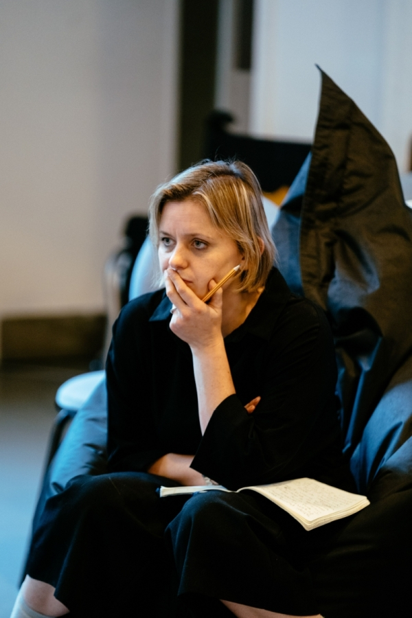 Image description: A woman with a blonde bob in a side parting. She is sat on a chair, looking to the side with her chin resting in her hand and holding a pencil. She is in a rehearsal room.
