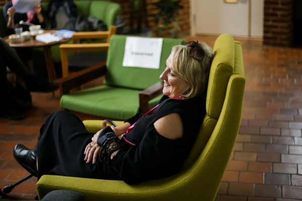 Image description: A woman with shoulder length blonde hair sits sideways in a lime green arm chair, her hands are crossed on her lap, she isn't looking at the camera.