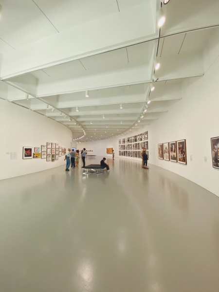 A curved room in an art gallery, with images lining the wall and viewers walking amongst the art.